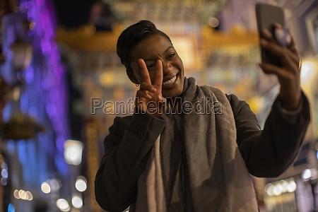 happy young woman taking selfie gesturing