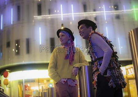 fashionable couple below neon city building