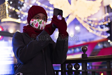 young woman in christmas mask taking
