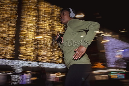 young woman with headphones jogging below