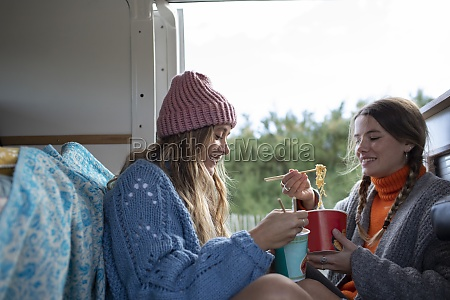 young women friends eating instant noodles