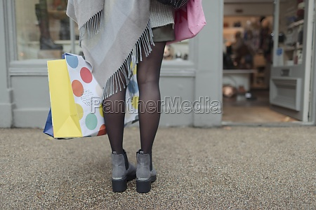 young woman with bags window shopping