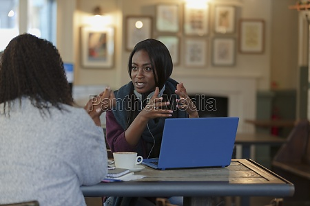 businesswomen talking at laptop in cafe
