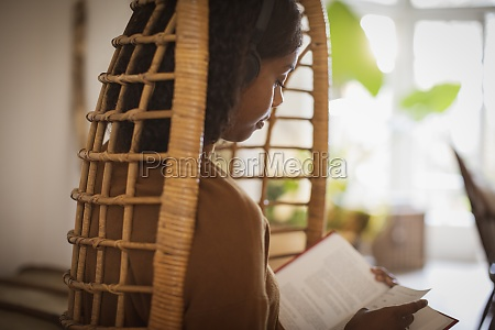 serene young woman with headphones reading