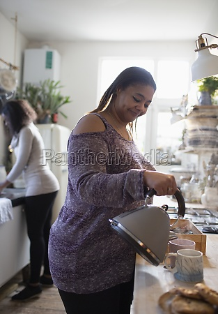 woman preparing tea in kitchen