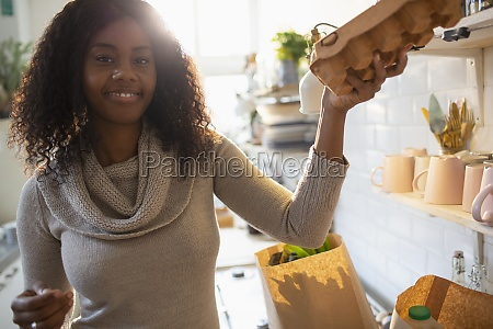 portrait smiling woman unpacking groceries in