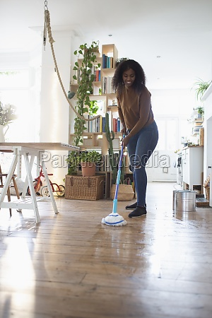 woman mopping hardwood floor in apartment