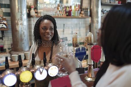 friendly female bartender serving white wine