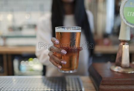 close up female bartender serving pint