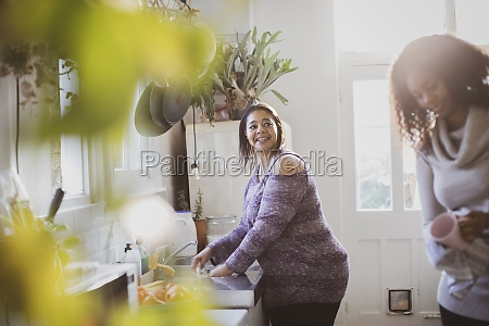 mother and daughter doing dishes in