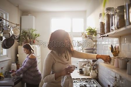 mother and daughter cleaning kitchen