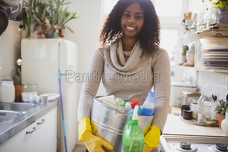 portrait smiling woman with cleaning supplies