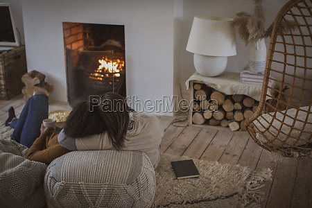 mother and daughter cuddling by fireplace
