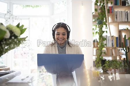 portrait happy woman with headphones working