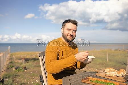 portrait happy man eating on sunny