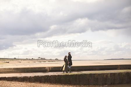 couple in winter coats walking on