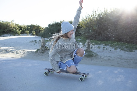 carefree young woman skateboarding on beach