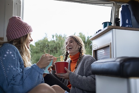 happy young women friends eating instant