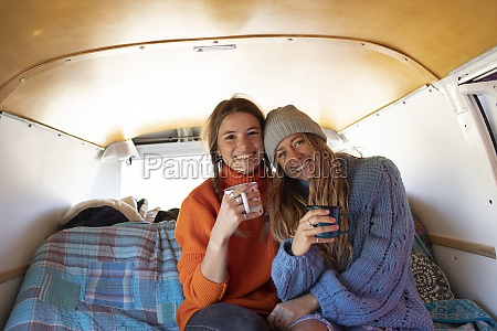 portrait happy young women friends drinking