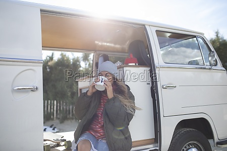 young woman drinking coffee in sunny