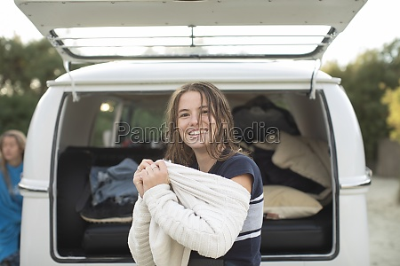 portrait happy young woman putting on