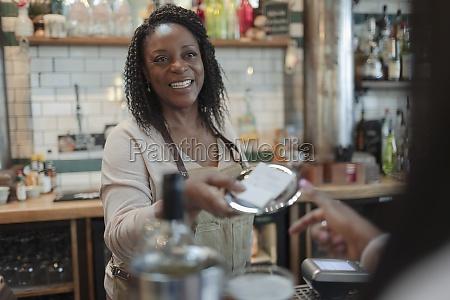 friendly female bartender giving bill to