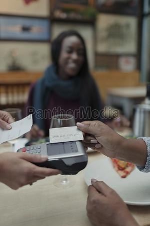 close up customer paying waitress with