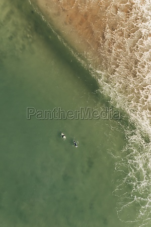 aerial view of two surfers riding