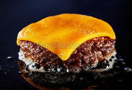 tasty cheeseburger with beef patty sizzling