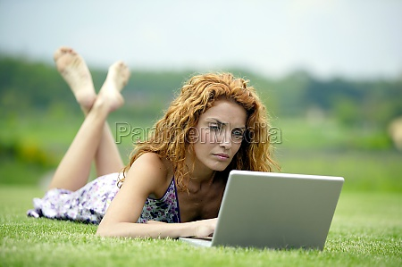 woman with laptop on meadow