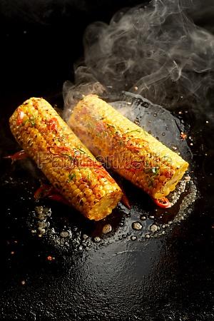 tasty corn cobs preparing on hot