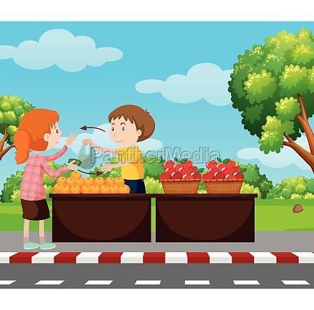 boy selling fruits on pavement