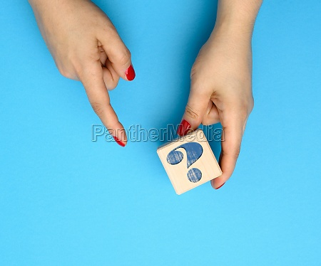 female hand holding a wooden cube