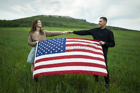 young couple holding american flag in