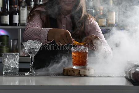 barkeeper serving cocktail at bar counter