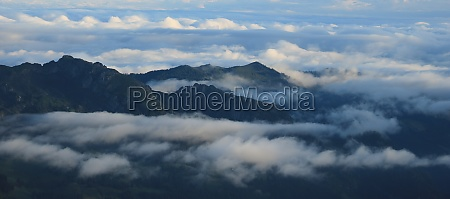fog and clouds surrounding green hills