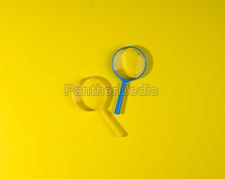 two plastic magnifiers on a yellow