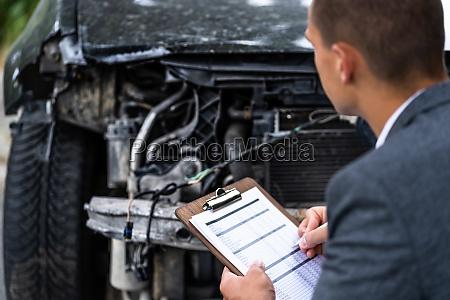 insurance agent examining car