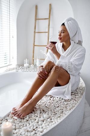 attractive woman in bathrobe sitting near