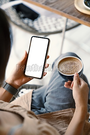 woman holding smart phone showing white