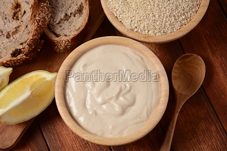 tahini and sesame seeds in wooden
