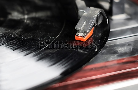 the needle of a turntable playing