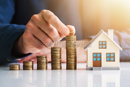 businessman arranging stacked coins near house