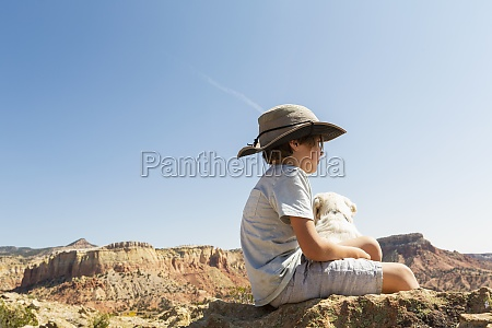 young boy sitting on rock with