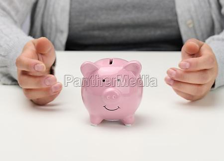 female hands and pink ceramic piggy