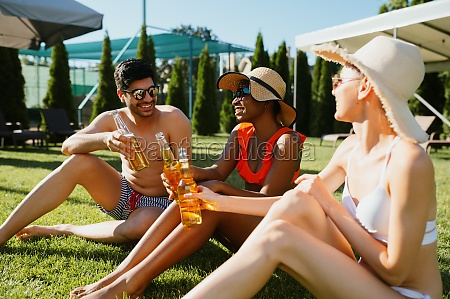 cheerful friends drink beer near the