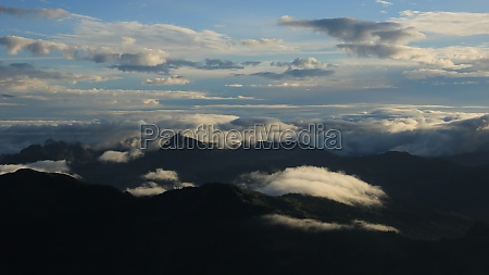 bright lit clouds over mountains in