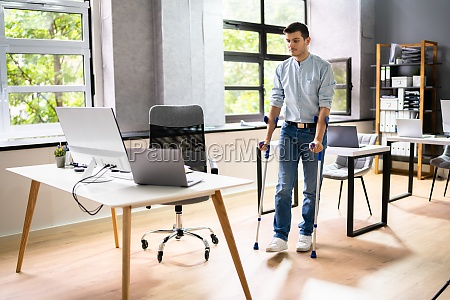worker with crutches at workplace or