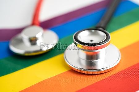 red stethoscope on rainbow flag background